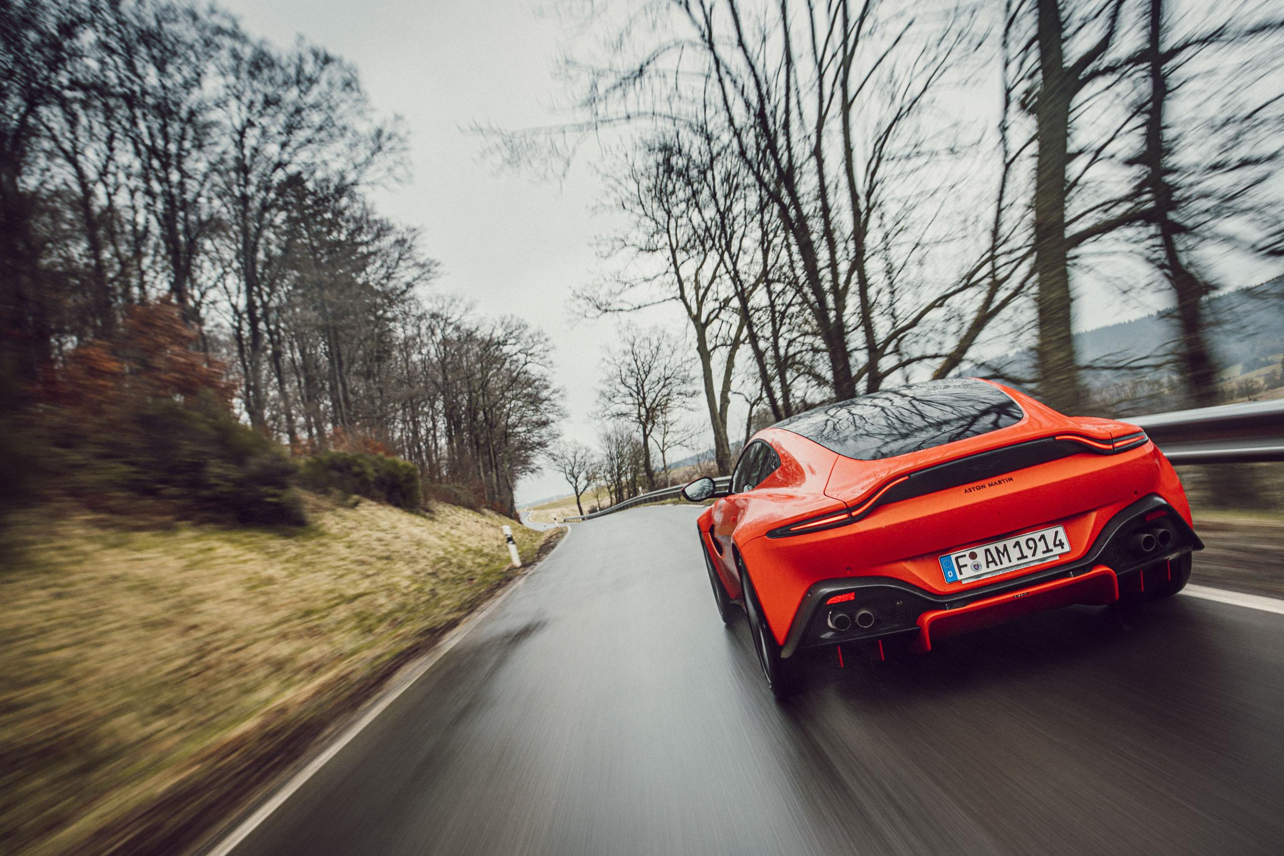 Roter Aston Martin Geneva während Regen bei der Fahrt von hinten