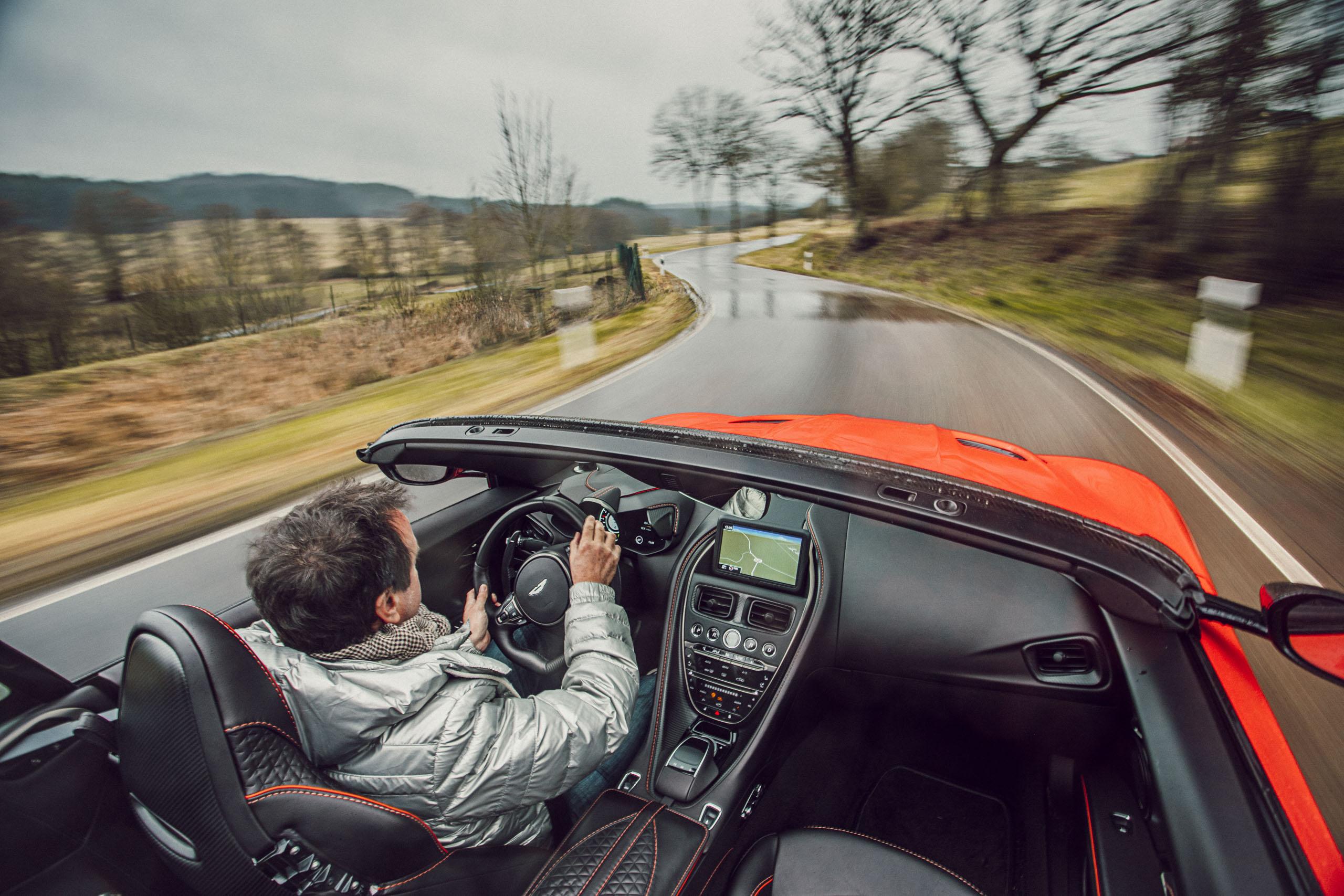Roter Aston Martin Geneva während Regen bei der Fahrt Innenraum