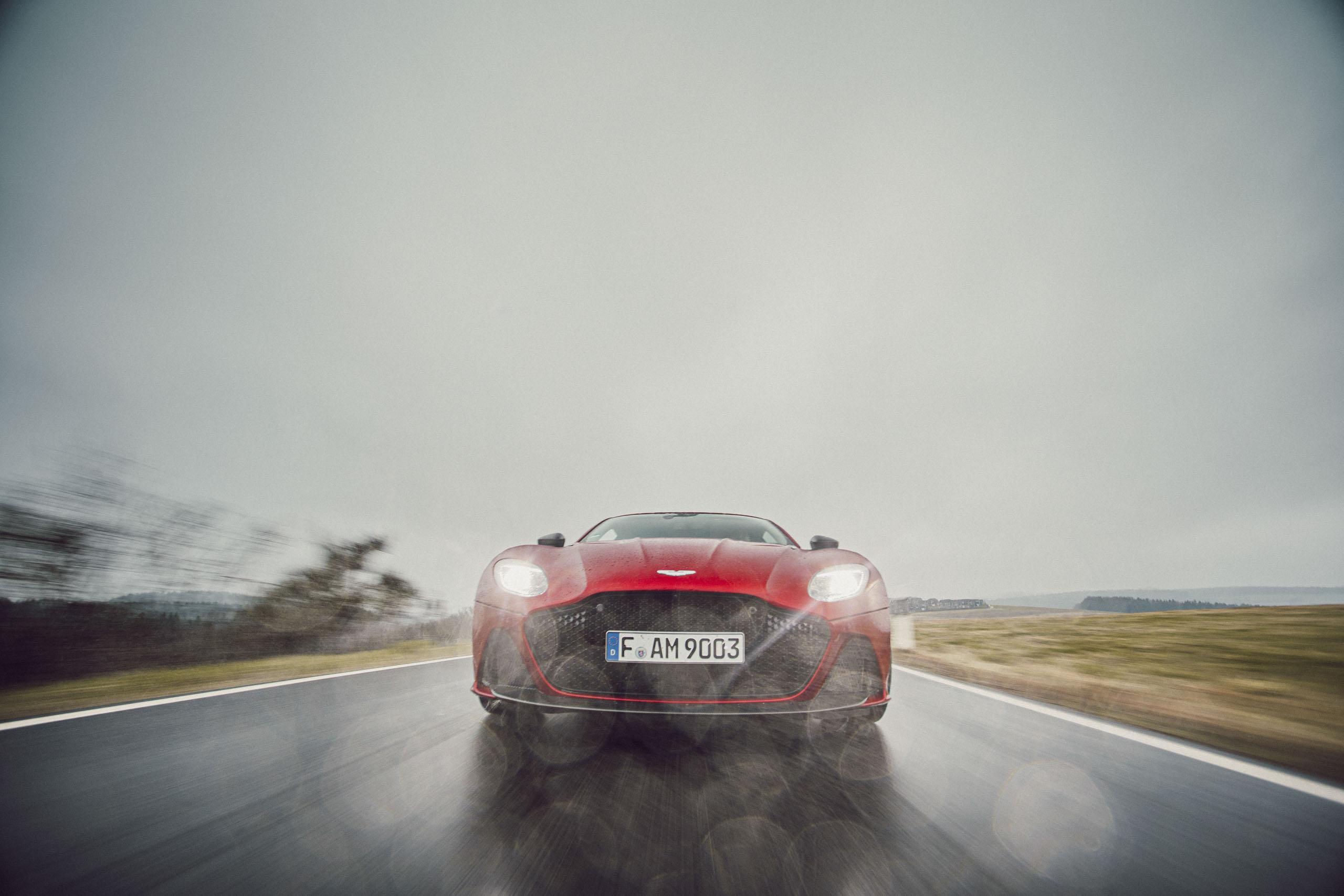 Roter Aston Martin Geneva während Regen bei der Fahrt Front