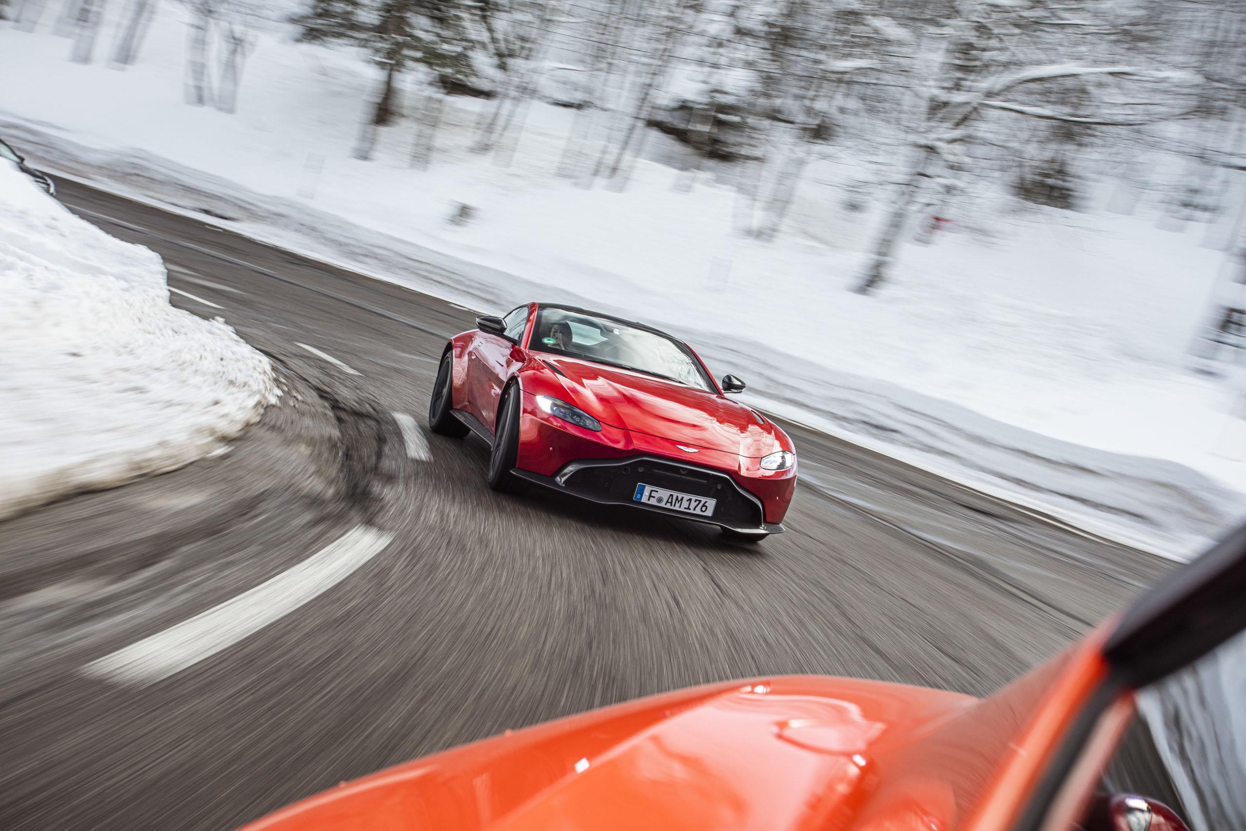 Roter Aston Martin Geneva bei Schnee in einer Kurve