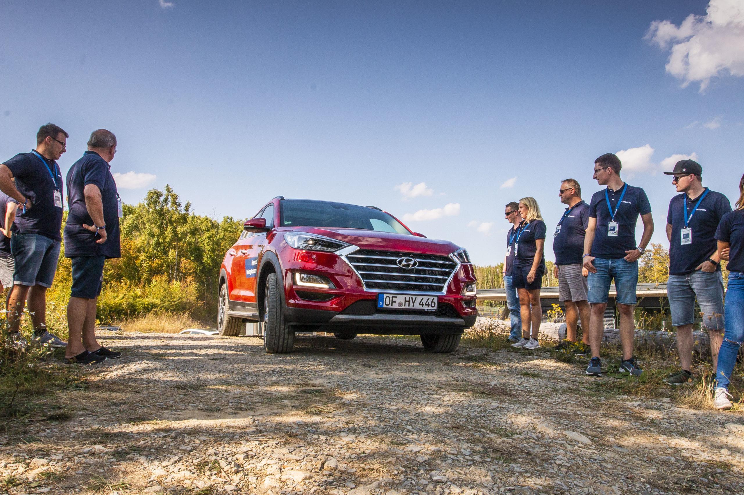 Roter Hyundai auf unebenem Weg mit Publikum